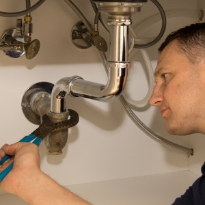 Plumber repairs kitchen sink