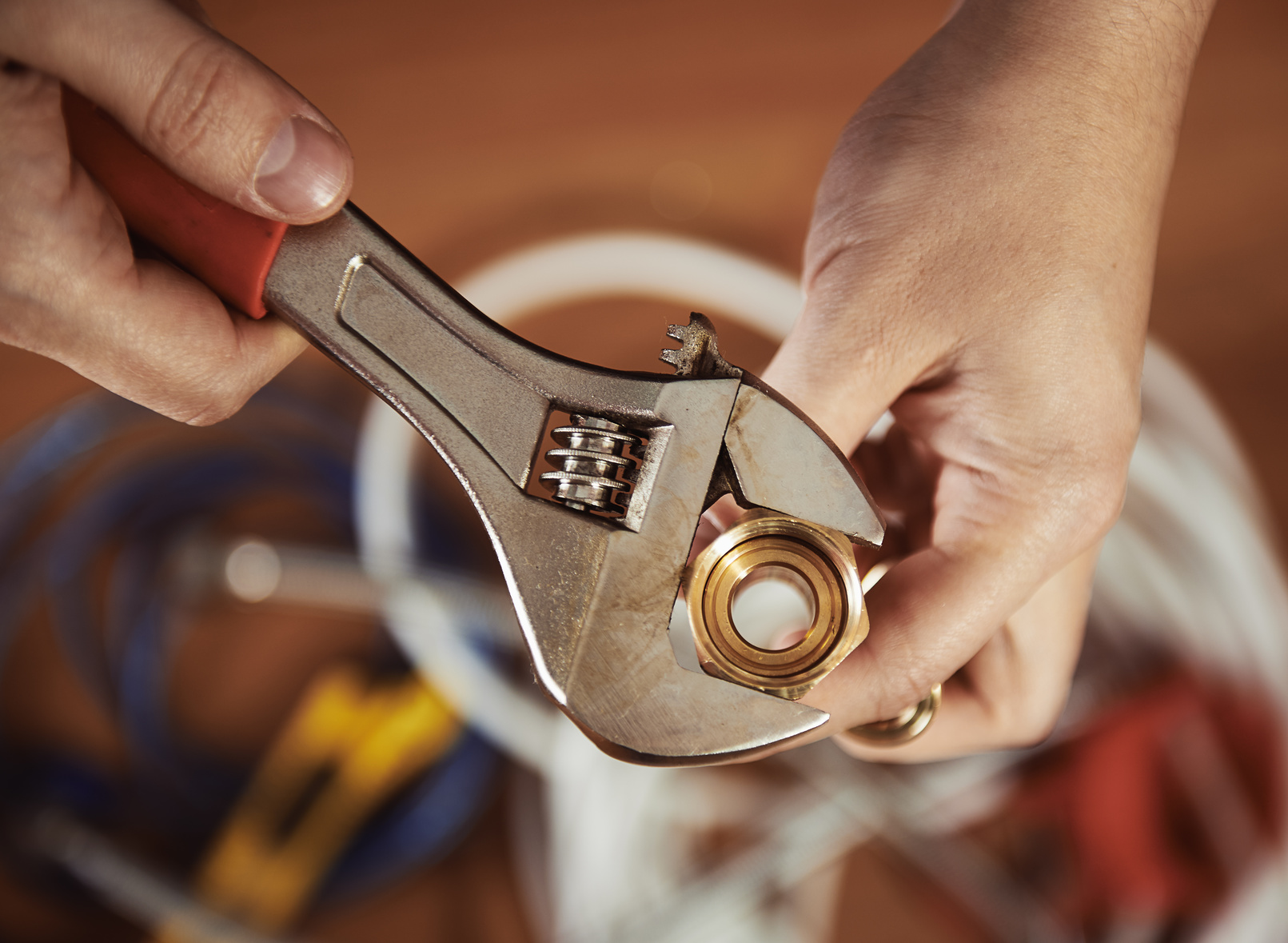 Close Up Of Plumber Hands Screwing Nut Of Pipe With Wrench